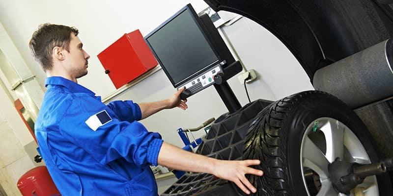 Mechanic balancing and aligning wheels
