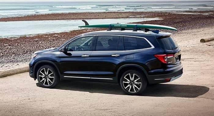 Honda Pilot Parked at Beach with Surfboard on Roof Rack