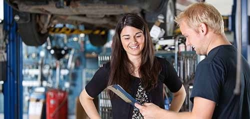 Mechanic Talking To A Woman About Car Repairs