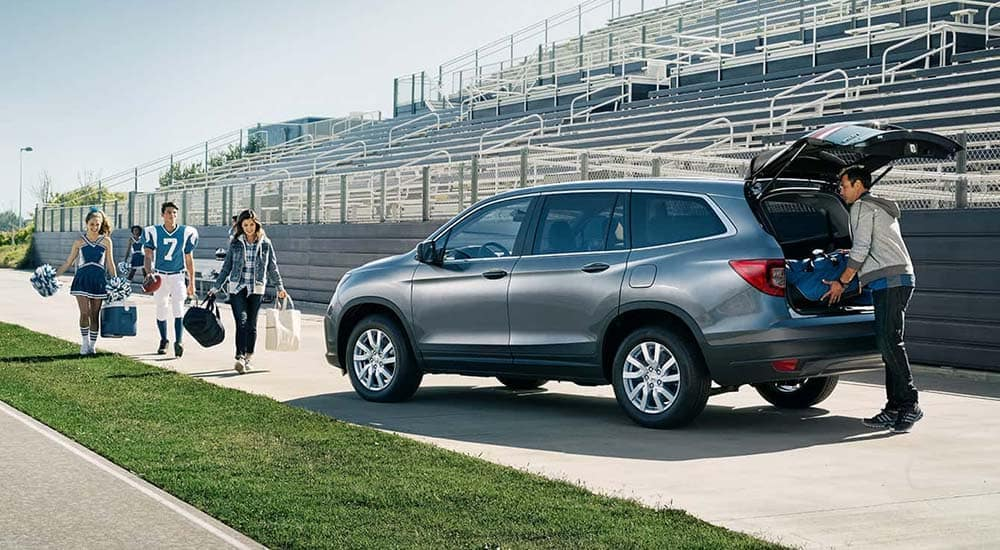 Family Loading Cargo Area of 2019 Honda Pilot Parked on Football Field