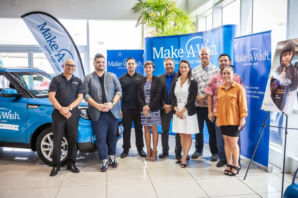 Triple J Auto employees stand with Make-A-Wish Guam employees