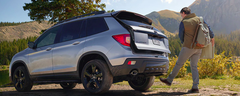 Man opening silver 2019 Honda Passport trunk with hands-free liftgate