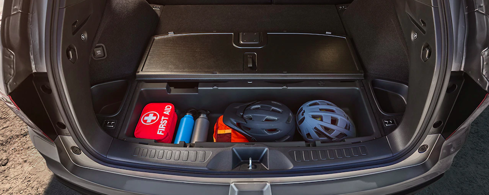 Bike helmets, water bottles, and first aid stored in additional cargo space in 2019 Honda Passport trunk