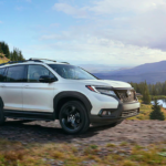White 2019 Honda Passport AWD in front of lake towing ATV