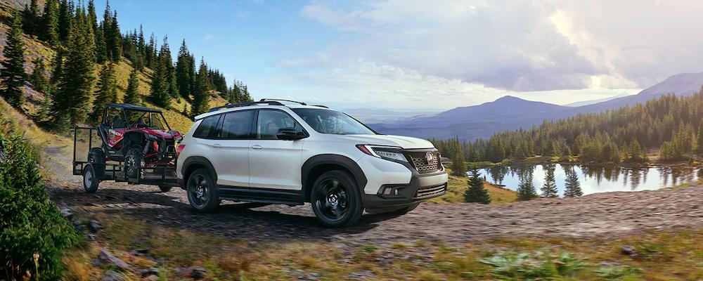 White 2019 Honda Passport AWD in front of lake towing ATV