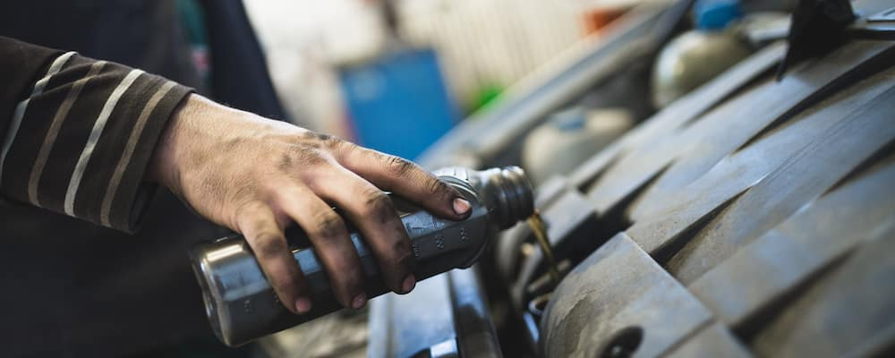Mechanic pouring oil from can into car engine