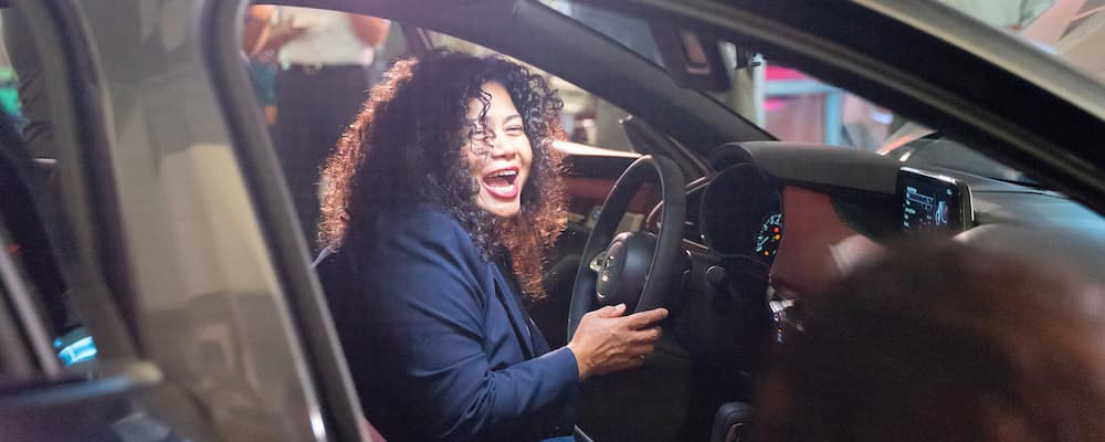 Woman laughing inside new 2020 Mazda3 driver's seat during release event