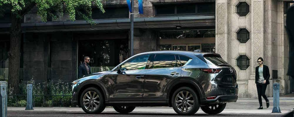 Silver Mazda CX-5 parked on the street in front of a concrete building with some greenery and pedestrians