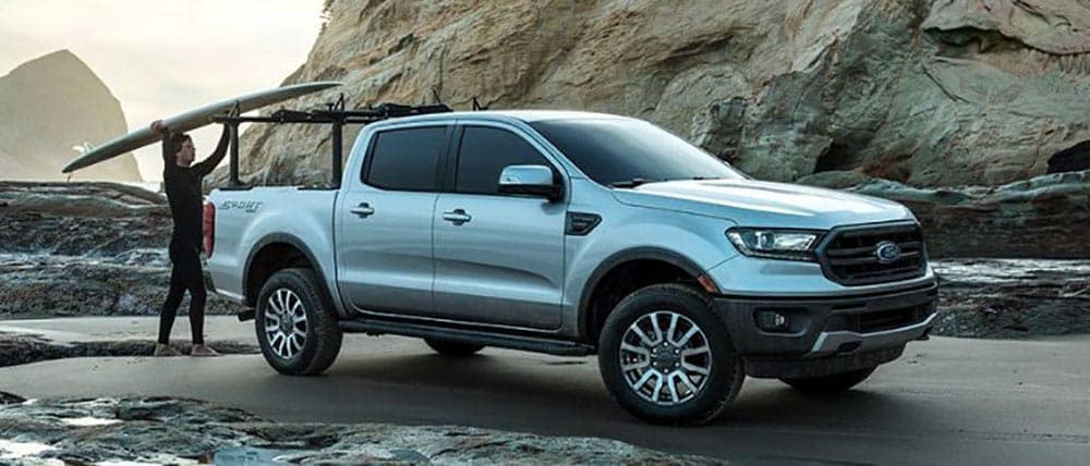 Surfer loading surf board into bed of 2019 Ford Ranger by rocky shore