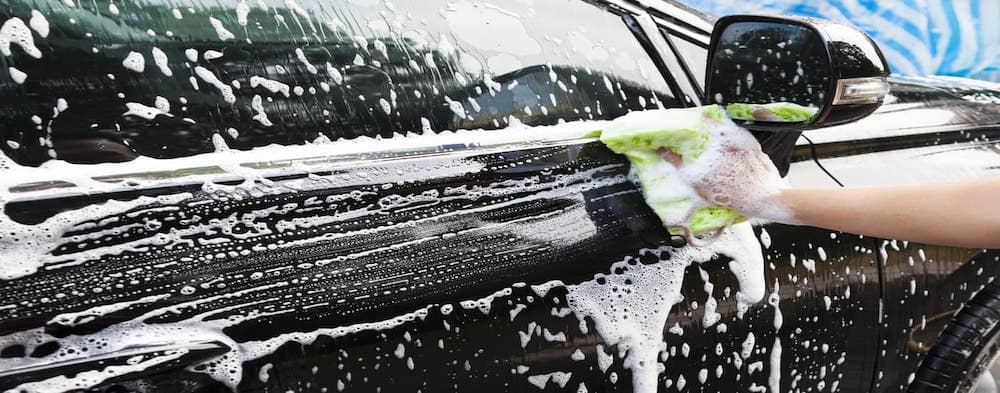 Washing black car with green cloth