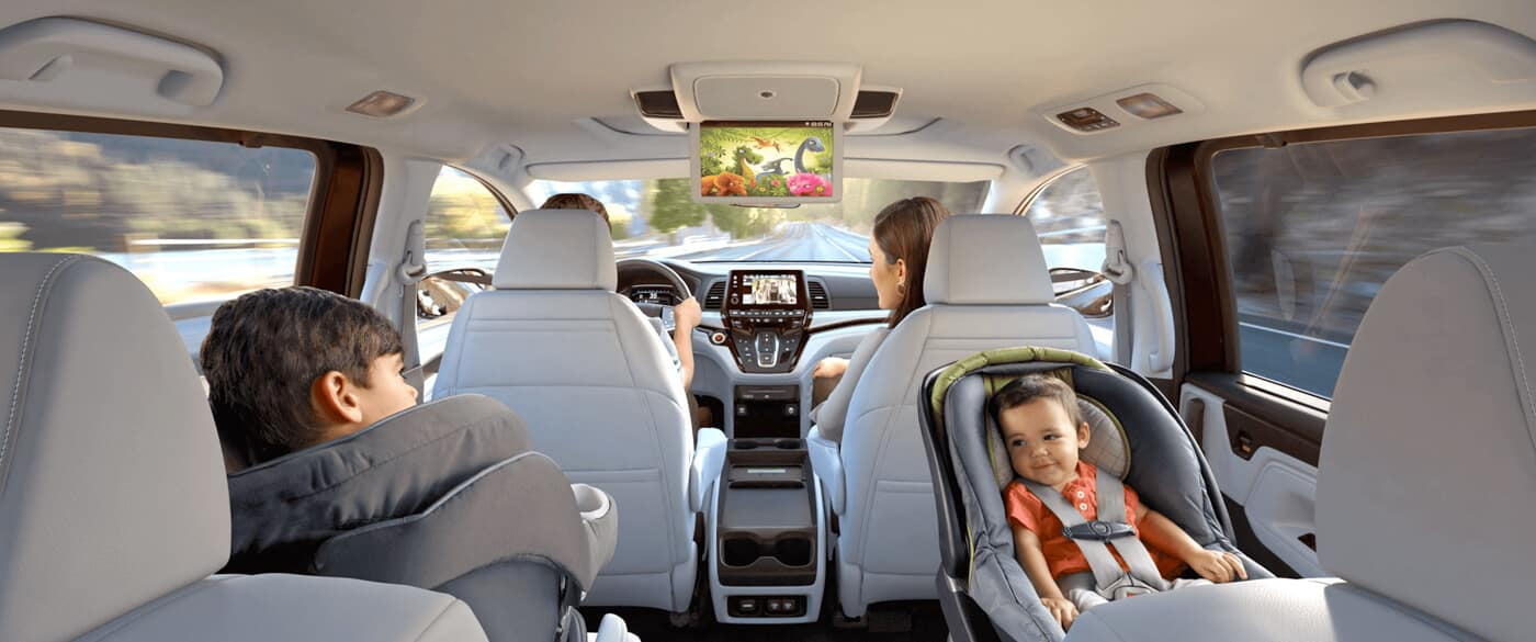 Kids in car seats watching rear entertainment system of 2020 Honda Odyssey