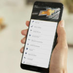 A white hand holding a smartphone with the Chevrolet Connected Services App pulled up.