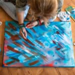 Woman sitting on the floor painting an abstract canvas
