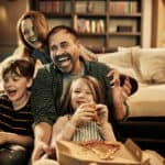 Close up of a family watching a movie while having pizza