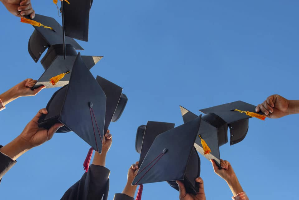 Students tossing graduation caps into the sky