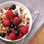 High angle shot of granola, yoghurt and berries in a bowl