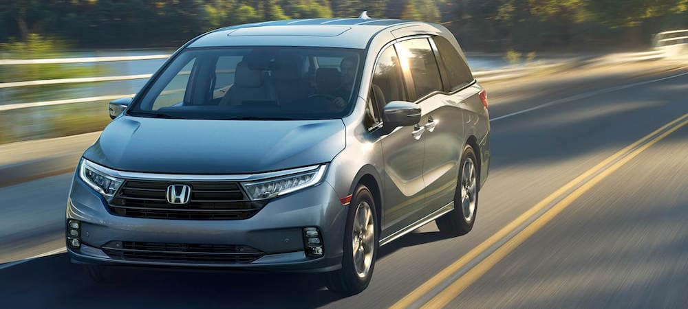Silver 2021 Honda Odyssey driving on road with blurred background
