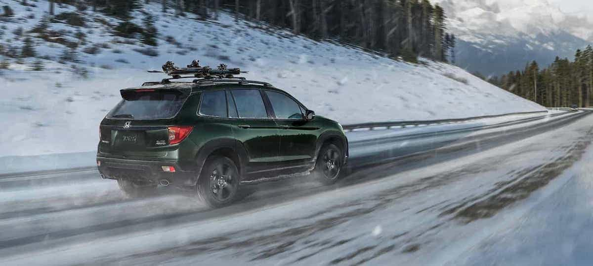 Green 2020 Honda Passport with AWD and Intelligent Traction Management driving on snowy road with roof rails
