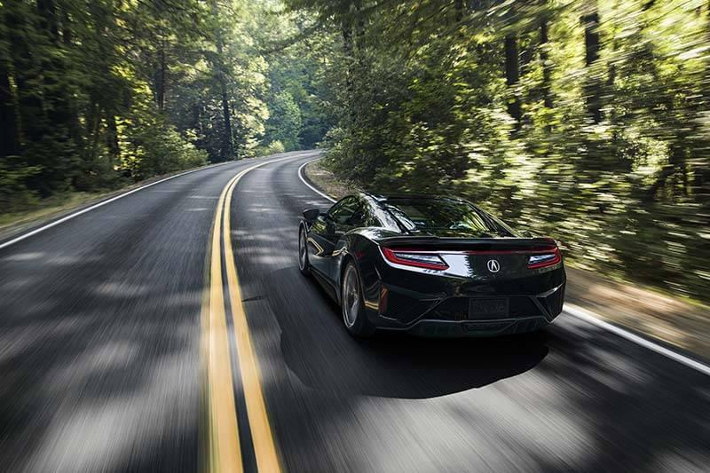Acura NSX driving along a curved road