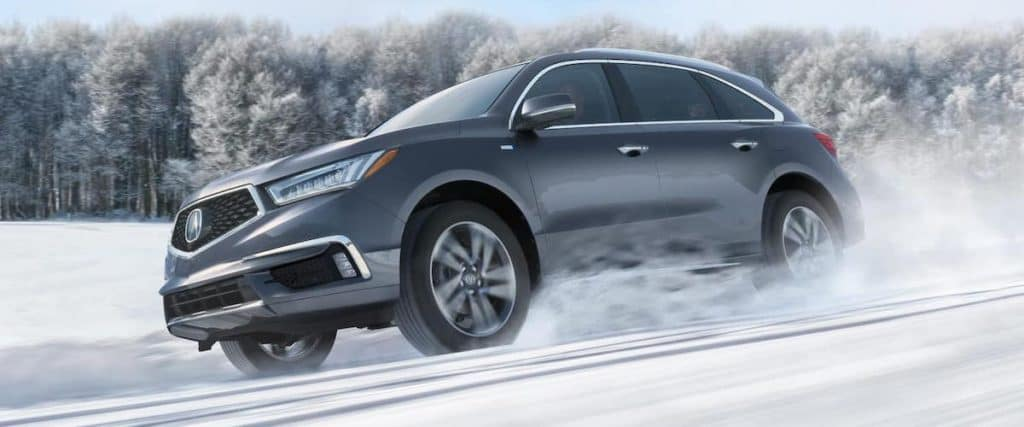 Low side angle on dark silver 2020 Acura MDX with AWD driving down snowy hill road