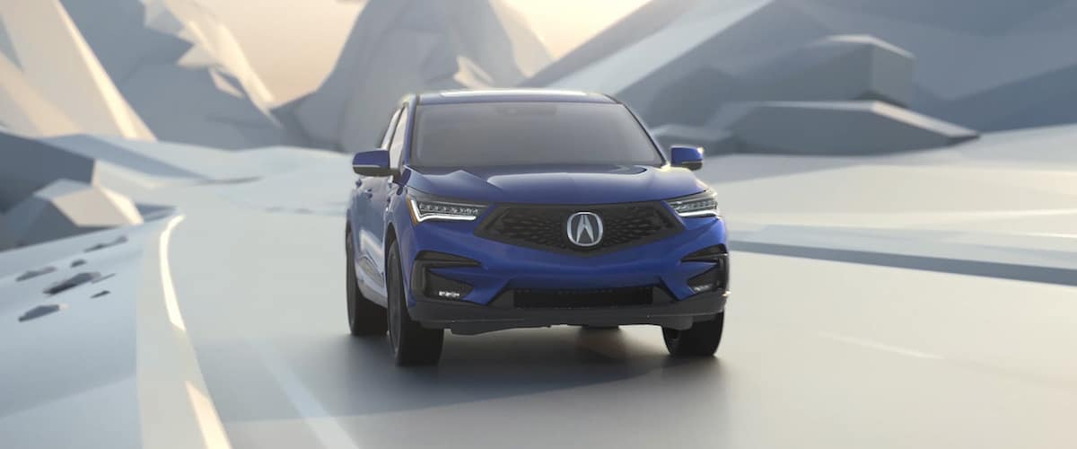 Blue 2021 Acura RDX SH-AWD front view driving through mountain concept