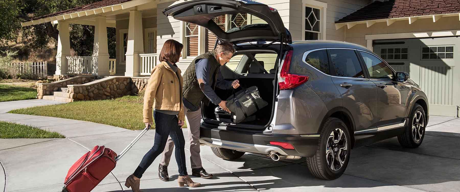 Couple loading luggage into cargo area of 2018 Honda CR-V