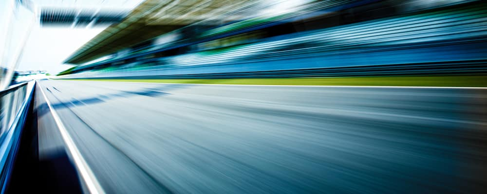 Blurred racetrack viewed from the driver's seat of a high-performance vehicle