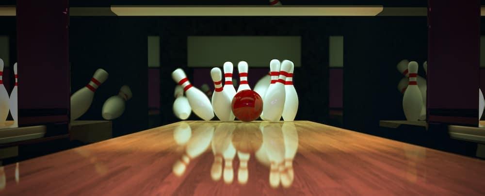 Red bowling ball hitting bowling pins