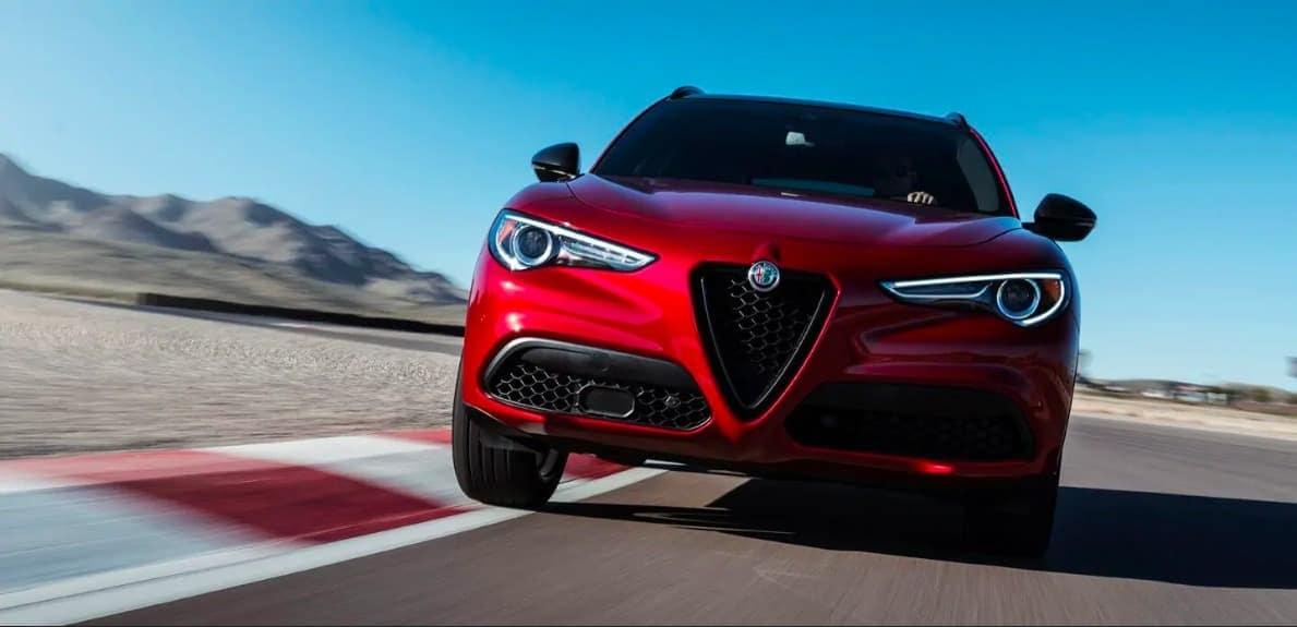 2019 Alfa Romeo Stelvio in red driving fast down the road