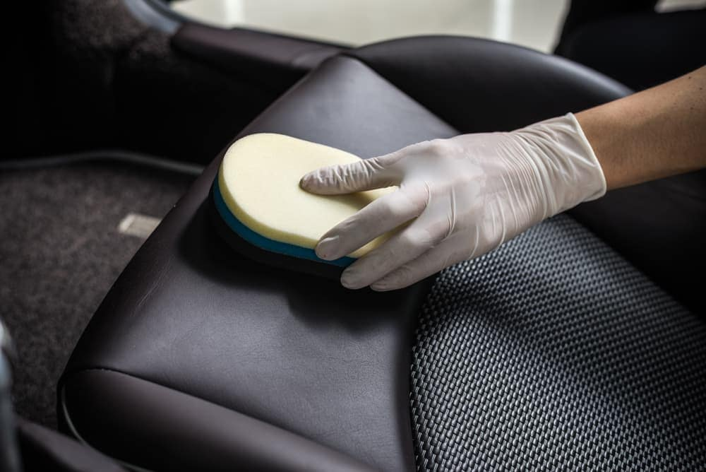 Cleaning leather car seat with brush